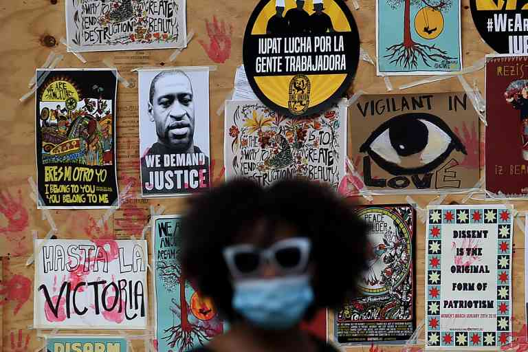 TOPSHOT - A demonstrator walks past a mural for George Floyd during a protest near the White House in Washington, DC, on June 4, 2020. On May 25, 2020, Floyd, a 46-year-old black man suspected of passing a counterfeit $20 bill, died in Minneapolis after Derek Chauvin, a white police officer, pressed his knee to Floyd's neck for almost nine minutes. / AFP / Olivier DOULIERY