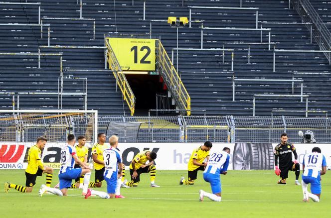 Les joueurs s'agenouillent en signe de solidarité avec les manifestations contre le racisme qui ont suivi la mort de George Floyd, avant le coup d'envoi du match de football de première division allemande BVB Borussia Dortmund contre Hertha Berlin, le 6 juin 2020, à Dortmund, dans l'ouest de l'Allemagne.