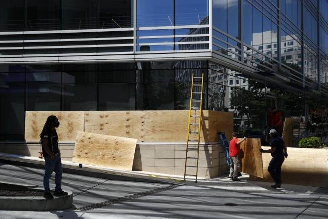 Des ouvriers du bâtiment protègent la façade d'un immeuble avant le passage de manifestants, à Washington, le 31 mai.