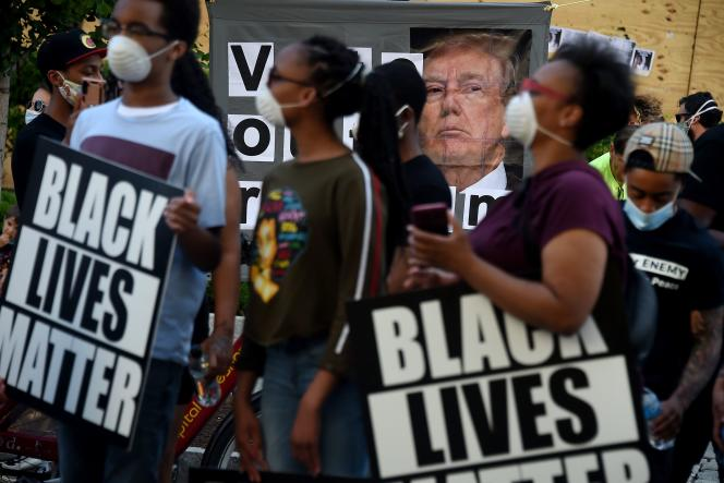 Des manifestants brandissent une pancarte avec une photo de Donald Trump, à Washington, le 7 juin.