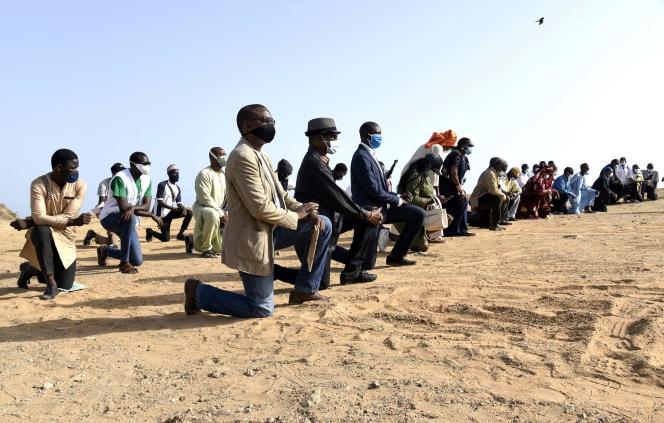 Des manifestants posent un genou à terre en hommage à George Floyd, sur la corniche de Dakar, le 9juin 2020.