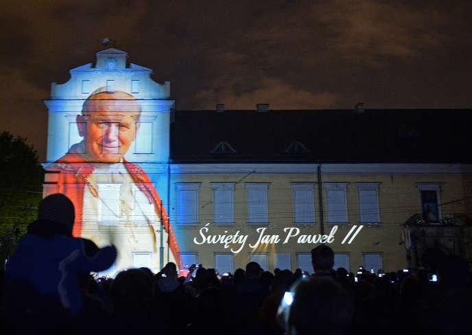 Une photo du pape Jean Paul II est projetée sur la façade du palais des évêques à Cracovie, lors de sa canonisation, en avril 2014.