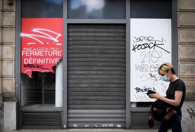 Une personne passe devant une boutique fermée, à Paris, le 8 juin.