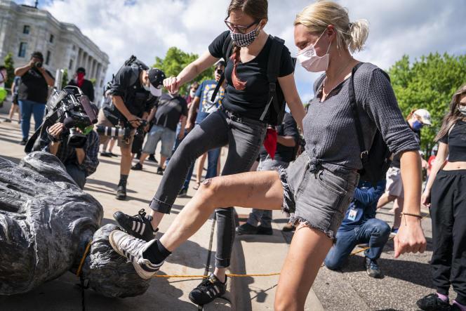 Des gens donnent s'en prennentà la statue de Christophe Colomb, après qu'elle a été renversée, devant le Capitole de l'État du Minnesota, le 10 juin.