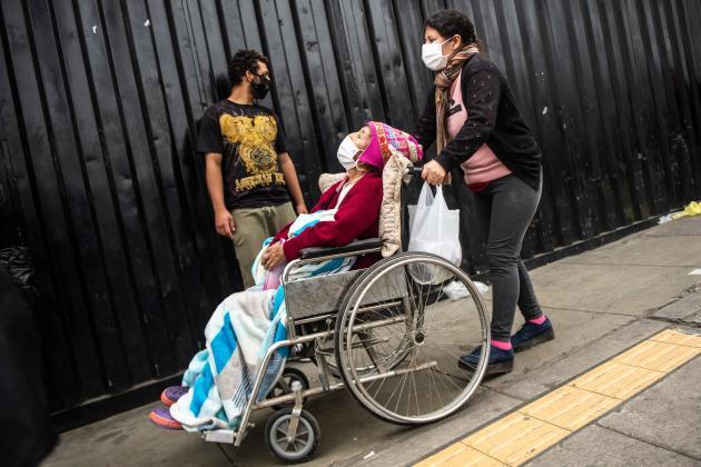 Une femme emmène sa mère malade au service des maladies respiratoires à l'hôpital Dos De Mayo à Lima, le 3 juin.
