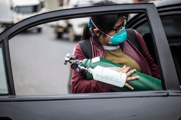 Devant l'hôpital Dos De Mayo à Lima, le 3 juin, une femme transporte une bouteille d'oxygène vide appartenant à un proche pour aller la remplir.