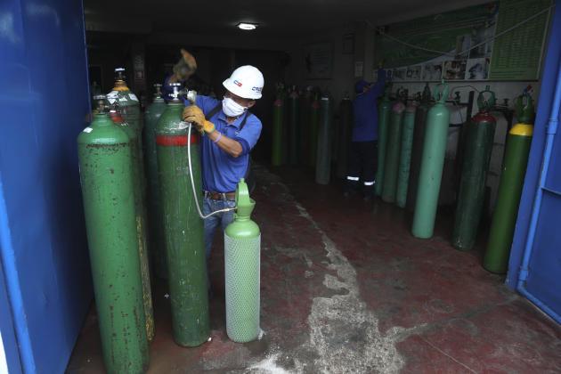Un employé rempli une bouteille d'oxygène, à Callao, le 3 juin.