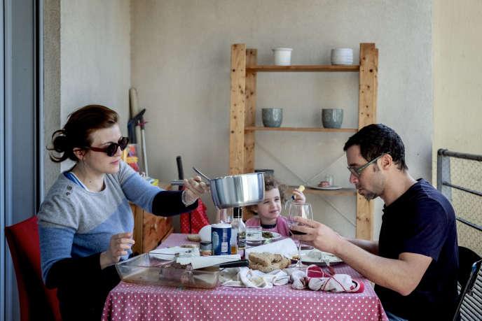 Anne-Lise, Bruno et Violette, 3 ans, partagent leur repas, au troisième jour de confinement, à Lyon, le19 mars.