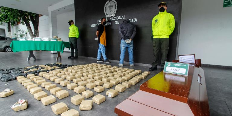 Two men who were arrested carrying in a hearse a coffin with drugs as if it belonged to a victim of the new coronavirus, are presented to the press next to packages of the seized drug in Cucuta, Colombia, in the border with Venezuela, on May 13, 2020. / AFP / Schneyder MENDOZA