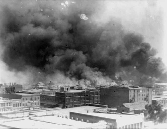 De la fumée s'échappe des immeubles de Tulsa, lors des émeutes raciales de 1921.