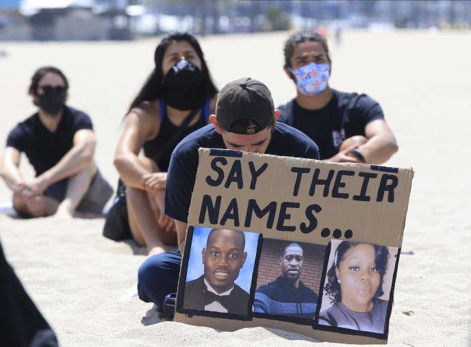Pancarte avec les photos d'Ahmaud Arbery, George Floyd et Breonna Taylo , lors d'une manifestation« Black Lives Matter» à Venice Beach, près de Los Angeles, le 12 juin 2020.
