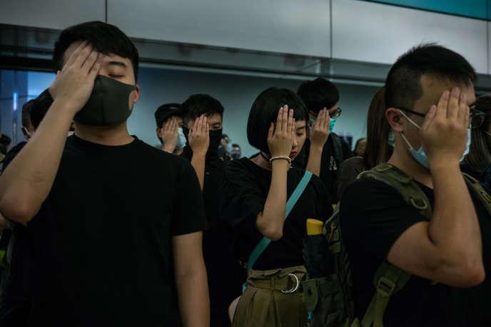 La main sur l'œil droit, des manifestants témoignent leur solidarité envers une infirmière blessée à l'œil dix jours plus tôt par un tir de la police à Hongkong, le 21 août 2019.