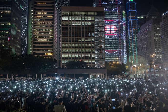 Des lycéens brandissent la lumière de leurs téléphones lors d'une manifestation contre le gouvernemen, dans le centre-ville de Hongkong, le 22 août 2019.