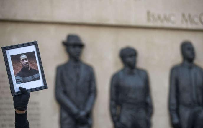 Le 30 mai, un manifestant brandit une photo de George Floyd devant le Clayton, Jackson, McGhie Memorial dans le cadre d'une grande manifestation à Duluth, Minnesota.