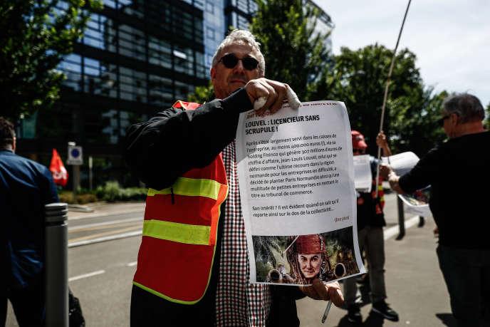 Un syndicaliste tient une affiche dénonçant les pratiques supposées de Jean-Louis Louvel, devant le tribunal de commerce de Rouen, mardi 9 juin, en pleine procédure de rachat du quotidien «Paris-Normandie».