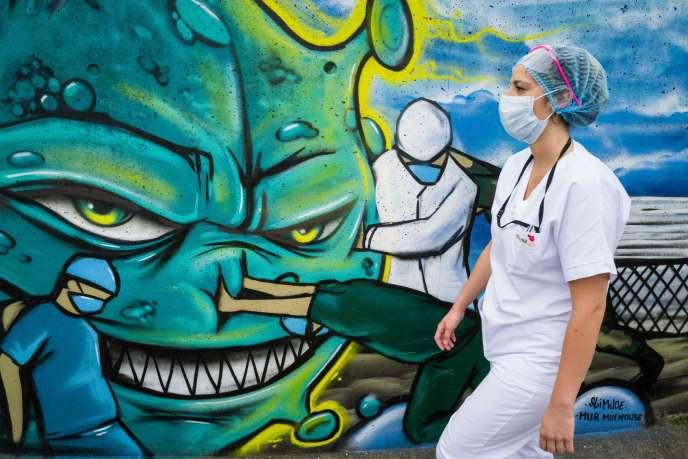 Devant une fresque représentant une infirmière, un médecin et un soldat luttant contre la pandémie du Covid-19, le 22 mai à Mulhouse (Haut-Rhin).