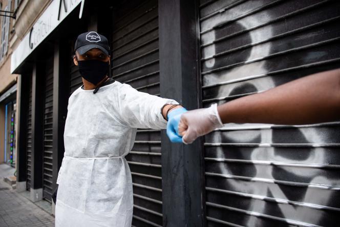 Sur le Vieux-Port de Marseille, deux personnes saluent en respectant les gestes barrières pour lutter contre la propagation de l'épidémie de Covid-19, le 17 mai.