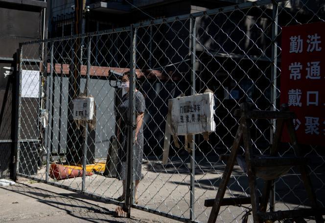 Une femme attend une livraison, dans une zone résidentielle en quarantaine, près du marché deXinfadi, le 14 juin à Pékin.