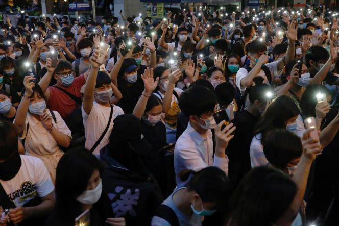 Des manifestants brandissent leur téléphone portable pour commémorer le premier anniversaire de la mobilisation à Hongkong, le 9 juin.