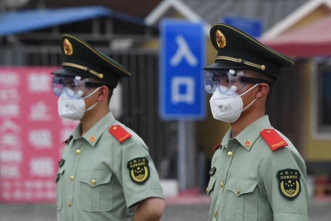 Des agents de la police paramilitaire montent la garde, devant le marché fermé deXinfadi, le 13 juin à Pékin.