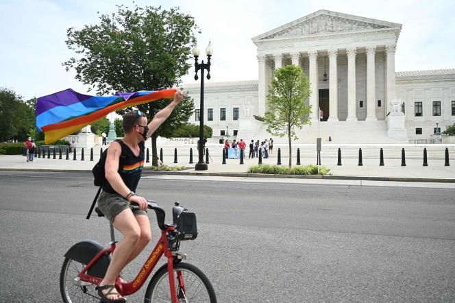 Un homme brandit un drapeau arc-en-ciel devant la Cour suprême des Etats-Unis, lundi 15juin.
