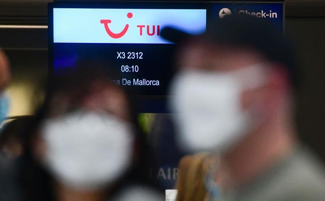 Des passagers attendent, au guichet de la compagnie TUI, d'embarquer dans leur avion pour Palma de Majorque, à l'aéroport de Düsseldorf, le 15 juin.