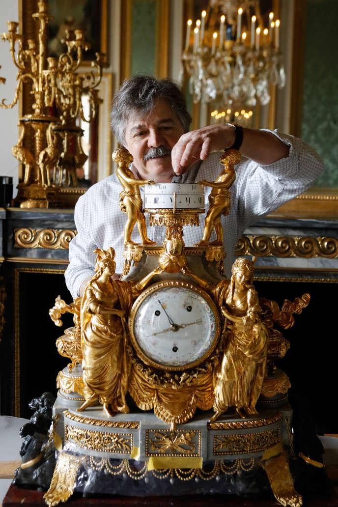 Bernard Draux, en 2019, aux petits soins de la pendule aux sultanes, dans la chambre à coucher de Marie-Antoinette, au château de Versailles.