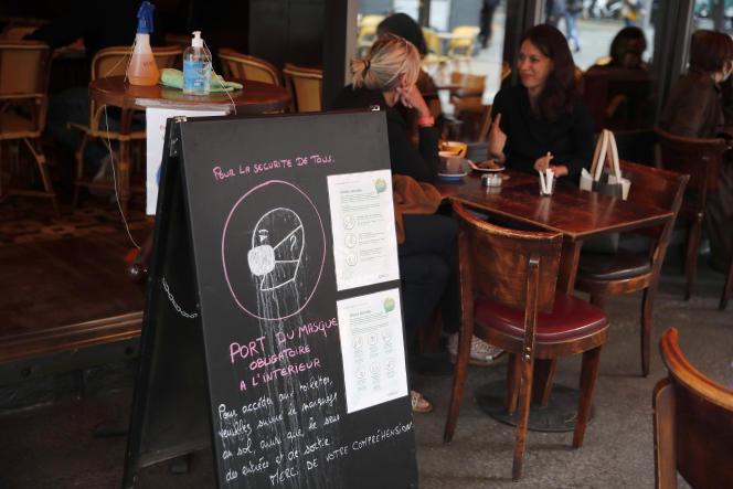 Une pancarte avec des instructions sur les gestes barrières, placée sur une terrasse d'un restaurant, à Paris, le 15 juin 2020.