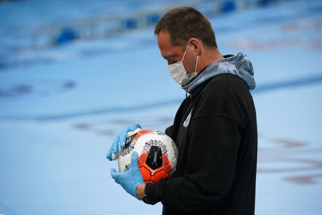 Un membre du staff portant des équipements médicaux nettoie un ballon avant le match de football de Premier League entre Manchester City et Arsenal, le 17 juin.