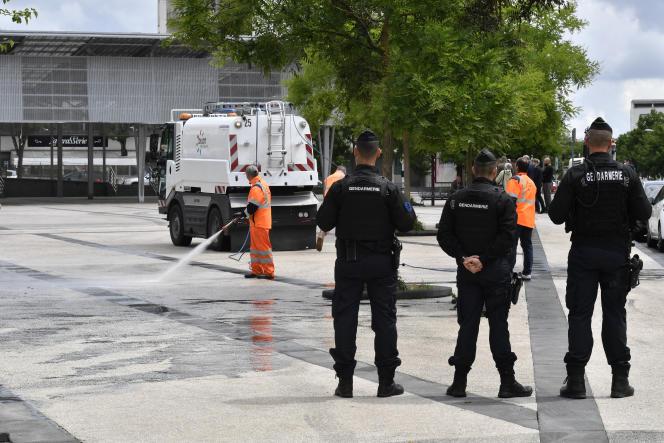 Des gendarmes protègent les employés municipaux qui nettoient le quarter des Grésilles, à Dijon, le 16 juin.