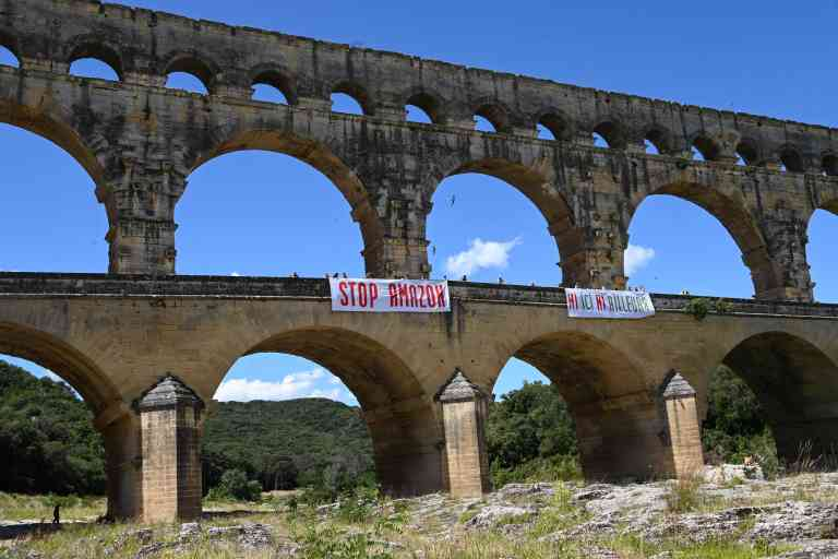 Activists from Attac France stands on the Pont du Gard bridge near two banners reading