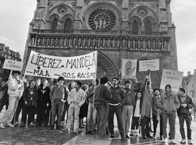 Harlem Désir, au centre, président de l'association SOS-Racisme, pendant une manifestation de soutien à Nelson Mandela, à Paris, le 25décembre 1985.