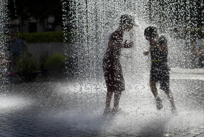 A Vilnius (Lituanie), des enfants se rafraîchissent dans une fontaine publique, alors que le thermomètre dépasse les 32 °C, le 19 juin 2020.