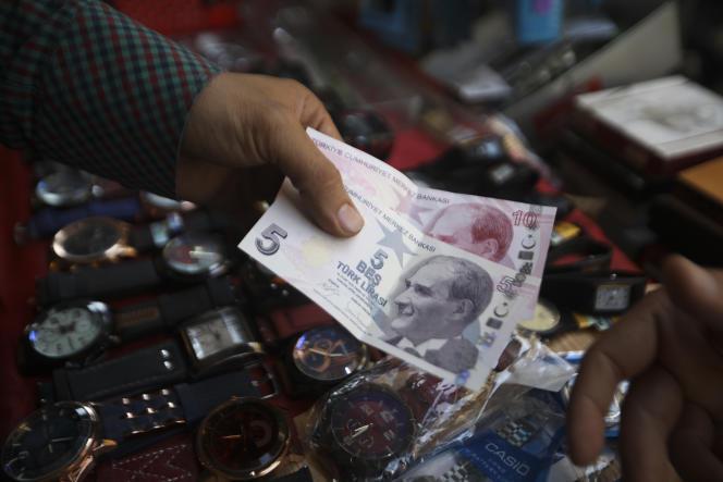 Un homme tend des livres turques à un vendeur pour payer sa marchandise, à Idlib (Syrie), le 20 juin.