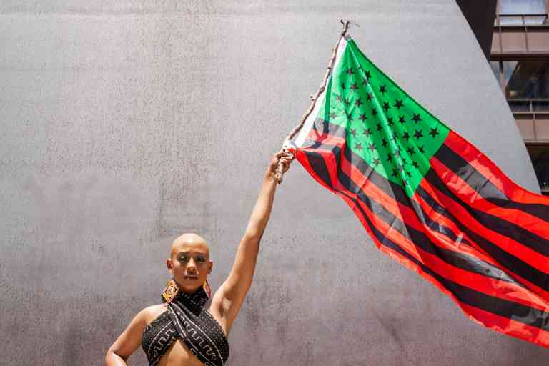 CHICAGO, ILLINOIS - JUNE 19: Performer Keya Trammell waves the Black Liberation flag during the Million Man March on June 19, 2020 in Chicago, Illinois. Juneteenth commemorates June 19, 1865, when a Union general read orders in Galveston, Texas stating all enslaved people in Texas were free according to federal law.   Natasha Moustache/Getty Images/AFP == FOR NEWSPAPERS, INTERNET, TELCOS & TELEVISION USE ONLY ==