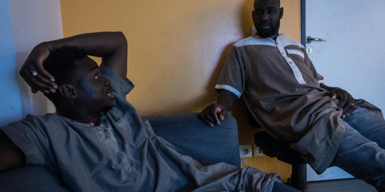 Moussa (à gauche) et Diaguely (droite) se reposent devant la télé avant d'aller travailler.