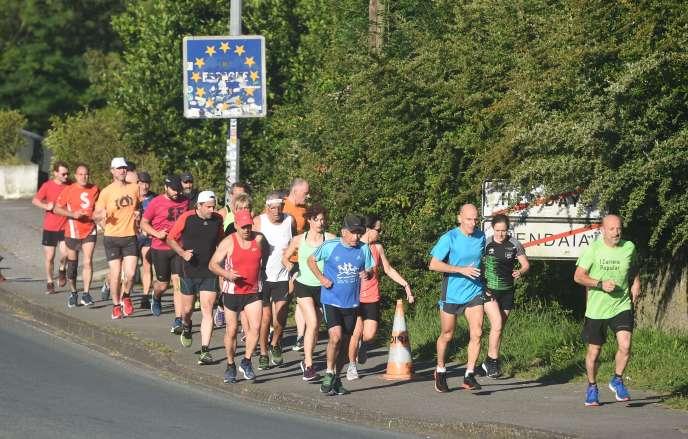 Un groupe de coureurs passe la frontière entre la France et l'Espagne, àAinhoa, au moment de la réouverture des frontières entre les deux pays, dimanche 21 juin.