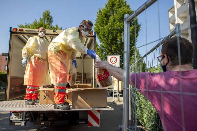 Après la découverte de nombreux cas de Covid-19 au sein de l'abattoir de Tönnies de Gütersloh (Rhénanie-du-Nord-Westphalie), des bénévoles de la Croix-Rouge distribuent du pain aux résidents deVerl, en proche banlieue, mise en quarantaine. Allemagne, dimanche 21 juin 2020.