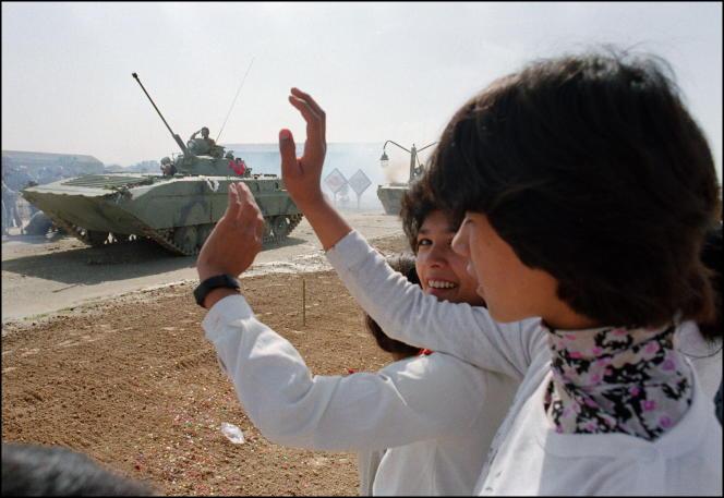 De jeunes Afghanes saluent un convoi de l'armée soviétique qui débute son retrait du pays, le17 octobre 1986 à Kaboul.