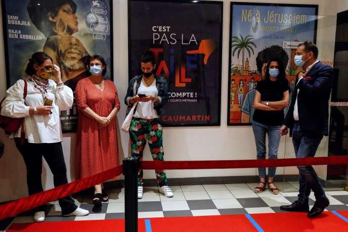 Des spectateurs masqués dans une file d'attente au cinéma 5 Caumartin à Paris, pour la réouverture des salles, le 21 juin au soir.