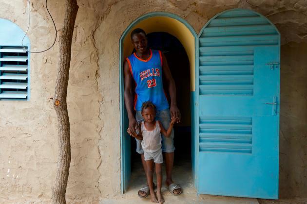 Kou Yao et sa fille dans leur nouvelle maison en voûte nubienne, dans le village de Ouroubonon, qu'il a construite avec l'aide de l'association.