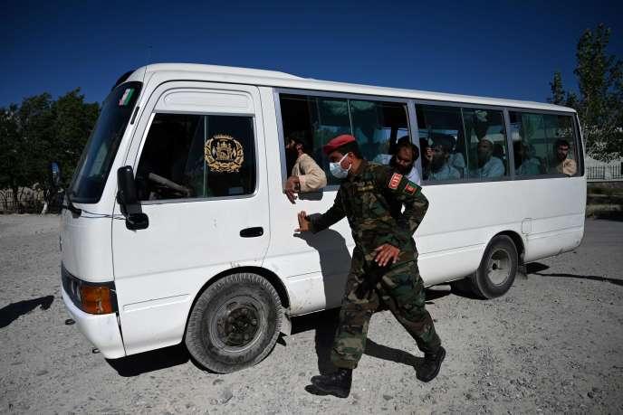 Un soldat de l'armée nationale afghane (ANA) escorte un bus transportant des prisonniers talibans libérés de la prison de Bagram, en Afghanistan,le 26 mai 2020.