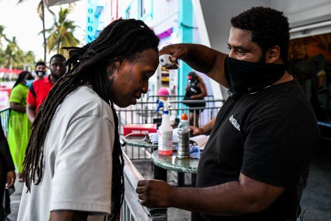 Prise de température à l'entrée d'un restaurant à Miami, le 24 juin.