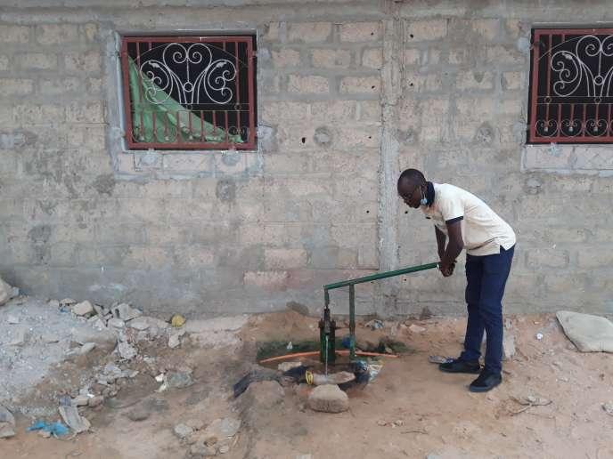 Quand l'eau ne coule même pas la nuit de son robinet, Papa Mbodj s'approvisionne auprès d'une pompe à eau traditionnelle, installée par ses voisins dans le quartier Comico Yeumbeul, dans la lointaine banlieue de Dakar, en juin 2020.