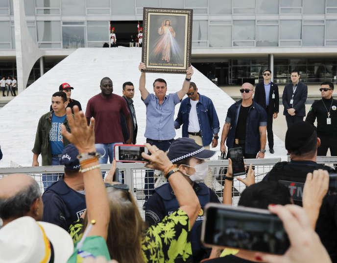Le président brésilien, Jair Bolsonaro, brandit une représentation de Jésus-Christ lors d'un rassemblement d'anti-IVG devant le Planalto, le 18 avril à Brasilia.