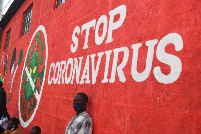 Un homme s'appuie sur le mur avec un graffiti sensibilisant au coronavirus Covid-19, à Nairobi le 6 juin.