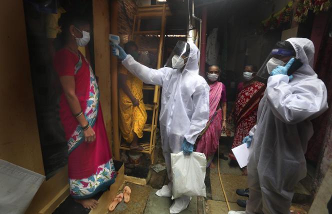 Une équipe de soignants en patrouille dans un bidonville de Bombay, en Inde, le 28 juin.