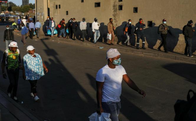 Des salariés de retour du travail, alors que l'Afrique du Sud commence à assouplir certaines règles du confinement, à Soweto, le 11 mai 2020.
