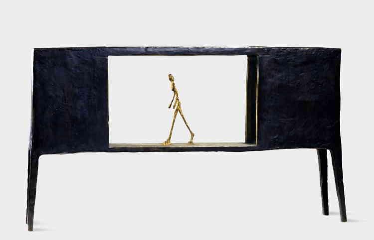 """«""""Figurine entre deux maisons"""" (1950) fait partie des œuvres d'après-guerre qui ravivent l'esprit surréaliste. Le motif de la cage, cher à Giacometti, réapparait ici par l'encadrement de la figure, qui met l'accent sur sa relation à l'espace et convoque la théâtralité. Le personnage est isolé, captif, coincé dans un univers absurde : une boîte ajourée sur pieds, évocation poétique de """"deux maisons"""". Elle est la dernière représentation sculptée d'une femme en mouvement chez Giacometti. »"""