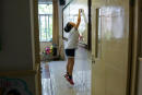 """In this photograph taken on September 27, 2017, a student cleans the whiteboard inside her classroom at her school in Shanghai. - Western interest in China's school system, and Shanghai in particular, has intensified after the city's pupils aced worldwide standardised tests in recent years. Teachers from England have been visiting to learn from Shanghai's success and the World Bank last year published a report titled, """"How Shanghai does it: Insights and lessons from the highest-ranking education system in the world"""". (Photo by Chandan KHANNA / AFP) / TO GO WITH China-school-education-children, FEATURE by Peter STEBBINGS"""